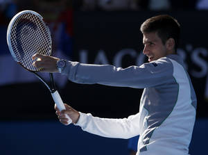 Photo - Serbia's Novak Djokovic impersonates his coach and former Grand Slam champion Boris Becker's service action following his fourth round win over Italy's Fabio Fognini at the Australian Open tennis championship in Melbourne, Australia, Sunday, Jan. 19, 2014. (AP Photo/Eugene Hoshiko)