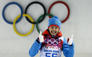 Photo - Second placed Russia's Olga Vilukhina gives a thumbs up during the flower ceremony after the women's biathlon 7.5k sprint, at the 2014 Winter Olympics, Sunday, Feb. 9, 2014, in Krasnaya Polyana, Russia. (AP Photo/Lee Jin-man)