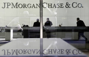 Photo - FILE - In this May 11, 2012 file photo, people stand in the lobby of JPMorgan Chase headquarters in New York. JPMorgan says it is facing a federal criminal probe relating to mortgage-backed securities sold before the financial crisis.  (AP Photo/Mark Lennihan, File)