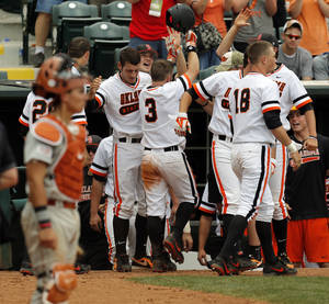 Photo - The OSU Cowboys celebrate the go-ahead run by Saulyer Saxon (3) in the eighth inning during a college baseball game between Texas and Oklahoma State in the Big 12 baseball tournament at the Chickasaw Bricktown Ballpark in Oklahoma City,  Saturday, May 24, 2014. OSU won 3-1 to force an elimination game. Photo by Nate Billings, The Oklahoman