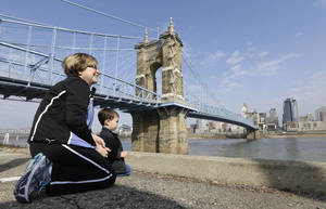 Photo - This April 9, 2013 photo shows Yvonne Parmley kneeling with her grandson, Finley MacKay, as they look towards downtown Cincinnati next to the Roebling Suspension Bridge over the Ohio River in Covington, Ky. The bridge was the model for New York City's Brooklyn Bridge. (AP Photo/Al Behrman)