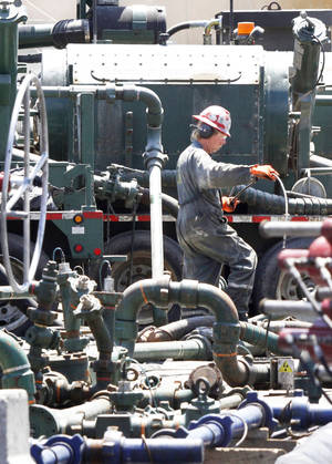 Photo - A worker walks past pipes connecting storage tanks and pumps in the hydraulic fracturing process July 27 in the Marcellus Shale layer to release natural gas.  AP Photo
