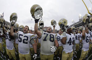 Photo - Georgia Tech's Trey Braun (78) and Will Jackson (52) and Tremayne McNair (46) celebrate after an NCAA college football game against the Syracuse Saturday, Oct. 19, 2013, in Atlanta. Tech won 56-0. (AP Photo/John Bazemore)
