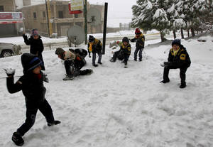 Photo - Syrian refugee children have a snowball fight at the mountain town of Bhamdoun, east of Beirut, Lebanon, Wednesday, Jan. 9, 2013. The fiercest winter storm to hit the Middle East in years has unleashed flash flooding, strong winds and a snowstorm that killed six people in the past few days, according to the Lebanese Red Cross. The Lebanese mountains have been covered with record snow fall that has brought traffic to a standstill and shut down mountain passes across the country. (AP Photo/Bilal Hussein)