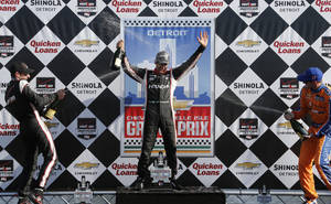 Photo - Helio Castroneves, center, celebrates his victory with Will Power, left, who finished second and Charlie Kimball, right, the third place finisher after the second race of the IndyCar Detroit Grand Prix auto racing doubleheader in Detroit Sunday, June 1, 2014.  (AP Photo/Bob Brodbeck)