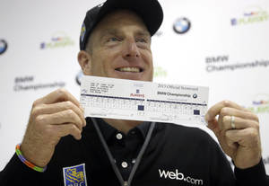 Photo - Jim Furyk holds up his scorecard after a news conference at the second round of the BMW Championship golf tournament at Conway Farms Golf Club in Lake Forest, Ill., Friday, Sept. 13, 2013. Furyk posted a single round 59, tying a PGA Tour record. (AP Photo/Charles Rex Arbogast)