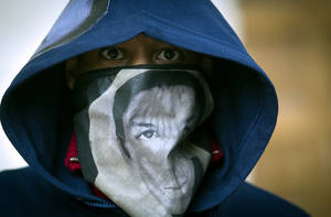"photo -   A man wears a hoodie and a scarf with the likeness of Trayvon Martin during a ""One Thousand Hoodies March for Trayvon Martin"" event Thursday, March 29, 2012 at the University of Minnesota campus in Minneapolis. Martin, a Florida teenager, was wearing a hoodie when he was shot and killed by a neighborhood watch volunteer. (AP Photo/The Star Tribune, Renee Jones Schneider) MANDATORY CREDIT; ST. PAUL PIONEER PRESS OUT; MAGS OUT; TWIN CITIES TV OUT"