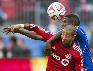 Photo - Toronto FC's defender Justin Morrow, front, and Colorado Rapids forward Edson Buddle battle for a header during first half MLS action in Toronto on Saturday, April 12, 2014. (AP Photo/The Canadian Press, Frank Gunn)