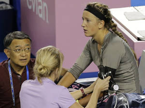 Photo -   Victoria Azarenka of Belarus, right, receives medical checkup in the third round match of the Japan Pan Pacific Open tennis tournament against Roberta Vinci of Italy in Tokyo, Wednesday, Sept. 26, 2012. Azarenka won 6-4, 6-2. (AP Photo/Shizuo Kambayashi)