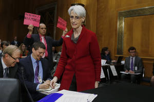 Photo - An anti war protestor holds up signs as Undersecretary of State for Political Affairs Wendy Sherman arrives on Capitol Hill in Washington, Tuesday, Feb. 4, 2014, to testify before the Senate Foreign Relations Committee hearing examining negotiations on Iran's nuclear program.  (AP Photo/Charles Dharapak)