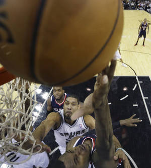 Photo - Atlanta Hawks' Shelvin Mack, right, shoots as San Antonio Spurs' Tim Duncan, center, defends him during the first half of an NBA basketball game, Monday,  Dec. 2, 2013, in San Antonio. (AP Photo/Eric Gay)