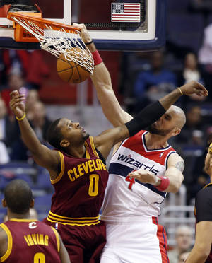 Photo - Washington Wizards center Marcin Gortat (4), from Poland, dunks the ball and takes it on the nose from Cleveland Cavaliers guard C.J. Miles (0) in the first half of an NBA basketball game on Friday, Feb. 7, 2014, in Washington. (AP Photo/Alex Brandon)