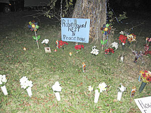 Photo - A makeshift for Robin Leander Howard at the base of a tree in the 1400 block of Monticello Court.  A candelight vigil honoring his life was held there Sunday night. <strong>MATT DINGER</strong>