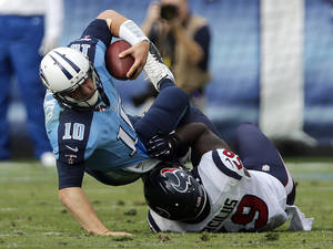 photo - Tennessee Titans quarterback Jake Locker (10) is sacked for a 1-yard loss by Houston Texans linebacker Whitney Mercilus (59) in the second quarter of an NFL football game on Sunday, Dec. 2, 2012, in Nashville, Tenn. (AP Photo/Joe Howell)