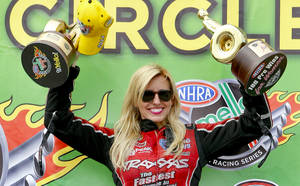 Photo - Funny Car driver Courtney Force hoists up her trophies for winning the NHRA Kansas Nationals auto race and being the 100th professional win for women drivers in the NHRA after defeating Cruz Pedregon in the finals at Heartland Park in Topeka, Kan., on Sunday, May 25, 2014. (AP Photo/The Topeka Capital Journal, Chris Neal)