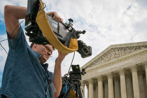 Photo - A videojournalist sets up outside of the Supreme Court in Washington, Tuesday, April 22, 2104. The court is hearing oral arguments between Aereo, Inc., an Internet startup company that gives subscribers access to television on their laptops and other portable devices and the over-the-air broadcasters. (AP Photo/J. David Ake)