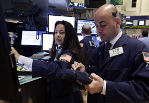 Photo - Specialist Wingszi Chiang, left, and trader Fred DeMarco work on the floor of the New York Stock Exchange Monday, April 28, 2014. Stocks are mostly higher in early trading as traders hope for another blockbuster merger in the health-care industry. (AP Photo/Richard Drew)