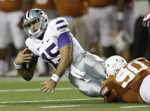 Photo - Kansas State's Jake Waters (15) is taken down by Texas' Malcom Brown (90) during the second half of an NCAA college football game on Saturday,  Sept. 21, 2013, in Austin, Texas. (AP Photo/Eric Gay)