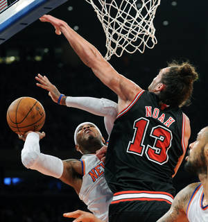 Photo - New York Knicks' Carmelo Anthony, left, attempts a shot as Chicago Bulls' Joakim Noah defends during the first quarter of an NBA basketball game Friday, Jan. 11, 2013, at Madison Square Garden in New York. (AP Photo/Bill Kostroun)