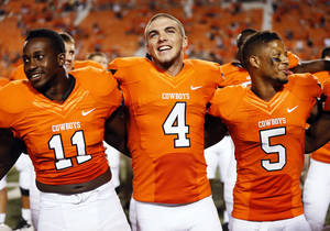 Photo - From left, Oklahoma State's Shaun Lewis, J.W. Walsh and Josh Stewart sing the alma mater after a college football game between the Oklahoma State University Cowboys (OSU) and the Lamar University Cardinals at Boone Pickens Stadium in Stillwater, Okla., Saturday, Sept. 14, 2013. OSU won, 59-3. Photo by Nate Billings, The Oklahoman
