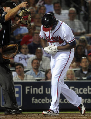 Photo - Atlanta Braves' Justin Upton, right, reacts after being hit by a pitch by starting pitcher Ubaldo Jimenez during the fifth inning of a baseball game on Thursday, Aug. 29, 2013, in Atlanta. Upton came out of the game on the play. (AP Photo/John Amis)