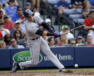 Photo - Colorado Rockies' Troy Tulowitzki singles in the eighth inning of a baseball game against the Atlanta Braves, Saturday, May 24, 2014, in Atlanta. (AP Photo/David Goldman)