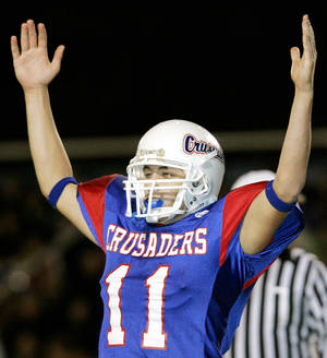 photo - Christian Heritage Academy's quarterback Justin Law celebrates after throwing a touchdown pass that put the Crusaders up 46-15 over  Community Christian School during the Oklahoma Christian School state championship game at Crusader Field in Oklahoma City on Nov. 10, 2005. Christian Heritage Academy beat Community Christian School 52-15 to win their 13th straight championship. By John Clanton/The Oklahoman.