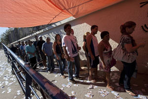 Photo -   People wait in line to vote in municipal elections outside a polling station in the Complexo da Mare slum in Rio de Janeiro, Brazil, Sunday, Oct. 7, 2012. Voters across Latin America's biggest country are electing mayors and municipal council members. (AP Photo/Silvia Izquierdo)