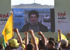 "Photo - Hezbollah supporters raise their hands to great Hezbollah leader Sheik Hassan Nasrallah, who delivers a speech through a giant TV screen from a secret location, during a rally marking the seventh anniversary of the 2006 Israel-Hezbollah war, at the southern Lebanese-Israel border village of Aita, Lebanon, Friday Aug. 16, 2013. Sheik Hassan Nasrallah says all preliminary investigations show Takfiri groups, a term for Sunni radicals, were likely behind Thursday's bombing in a predominantly Shiite southern suburb of Beirut that killed tens of people and wounded hundreds. The Arabic words on the left and right read:""Our decision is resistance."" (AP Photo/Mohammed Zaatari)"