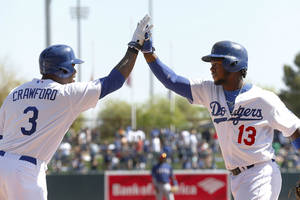 Photo - Los Angeles Dodgers' Hanley Ramirez (13) is congratulated by Carl Crawford after hitting a two-run home run against the Texas Rangers during an exhibition baseball game in Glendale, Ariz., Friday, March 7, 2014. (AP Photo/Paul Sancya)