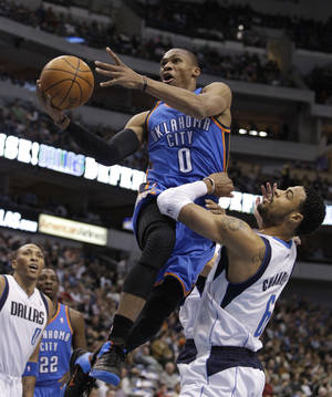Photo - Oklahoma City Thunder guard Russell Westbrook leaps past Dallas Mavericks center Tyson Chandler (6) for a shot in the first half of an NBA basketball game, Thursday, Jan. 6, 2011, in Dallas. (AP Photo/Tony Gutierrez)