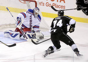 Photo - New York Rangers goalie Henrik Lundqvist (30) blocks a shot by Los Angeles Kings center Dwight King (74) in the third period of a preseason NHL hockey game, Friday, Sept. 27, 2013 in Las Vegas. The Kings won 4-1. (AP Photo/Julie Jacobson)