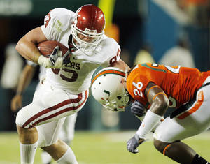 Photo - OU's Brody Eldridge (83) is tackled by Ray Ray Armstrong (26) after making a catch during the college football game between the University of Oklahoma (OU) Sooners and the University of Miami (UM) Hurricanes at Land Shark Stadium in Miami Gardens, Florida, Saturday, October 3, 2009. Photo by Nate Billings, The Oklahoman