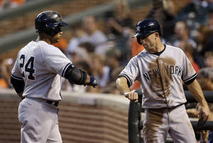 Photo - New York Yankees' Brett Gardner, right, fist-bumps teammate Robinson Cano after he scored a run against the Baltimore Orioles on Cano's ground out in the first inning of a baseball game, Wednesday, Sept. 11, 2013, in Baltimore. (AP Photo/Patrick Semansky)