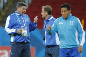 Photo - Luis Fernando Suarez, head coach of Honduras' soccer team, left, talks with an  assistant during a training session at the Estadio Beira-Rio in Porto Alegre, Brazil, Saturday, June 14, 2014. Honduras will play in E group of the Brazil 2014 World Cup. (AP Photo/David Vincent)