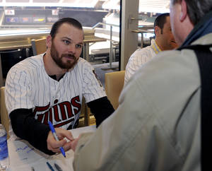 Photo - Minnesota Twins' Jason Kubel signs an autograph for a fan during the baseball team's TwinsFest at Target Field on Friday, Jan. 24, 2014, in Minneapolis. (AP Photo/Hannah Foslien)