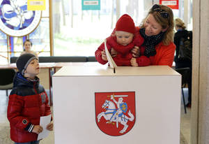 Photo - A woman with a child casts her ballot at a polling station during the first round of voting in presidential elections in Vilnius, Lithuania, Sunday May 11, 2014. (AP Photo/Mindaugas Kulbis)