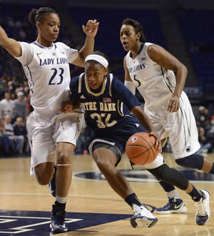 Photo - Notre Dame guard Jewell Loyd (32) drives to the basket past Penn State forward Ariel Edwards (23), left, and Penn State forward Talia East (5) in the first half of an NCAA college basketball game on Wednesday, Dec. 4, 2013, in State College, Pa. (AP Photo/John Beale)