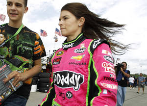 Photo - Driver Danica Patrick walks through the garage area before practicing for Sunday's NASCAR Sprint Cup series auto race at Kansas Speedway in Kansas City, Kan., Friday, Oct. 4, 2013. (AP Photo/Colin E. Braley)