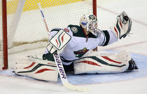 Photo - Minnesota Wild's Ilya Bryzgalov (30) makes a quick glove save against the Winnipeg Jets' during first period NHL hockey action in Winnipeg, Manitoba, Monday, April 7, 2014. (AP Photo/The Canadian Press, Trevor Hagan)