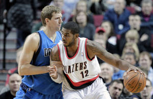 Photo - Portland Trail Blazers forward LaMarcus Aldridge, right, works the ball in on Dallas Mavericks forward Dirk Nowitzki, from Germany, during the first half of an NBA basketball game in Portland, Ore., Saturday, Dec. 7, 2013. (AP Photo/Don Ryan)