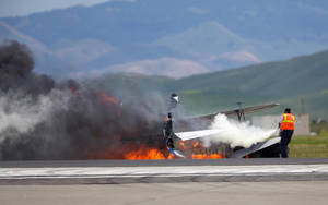 Photo - A worker fights a fire after a vintage biplane crashed upside-down on a runway at an air show at Travis Air Force Base in Fairfield, Calif., Sunday, May 4, 2014. The pilot, Edward Andreini, 77, of Half Moon Bay, was killed when the plane, flying low over the tarmac, crashed and caught fire. (AP Photo/Bryan Stokes)