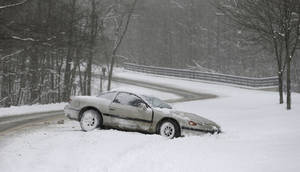 Photo - A car rests on the side of the road in the snow Friday, Feb. 1, 2013, in Solon, Ohio. Temperatures in northeast Ohio will remain in the teens Friday with a possibility of  three to five inches of new snow in areas. (AP Photo/Tony Dejak)