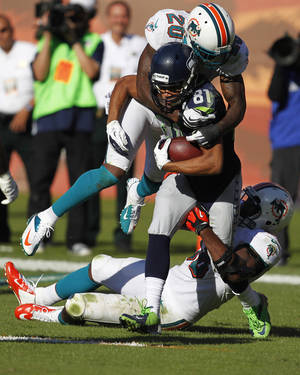 photo - Seattle Seahawks wide receiver Golden Tate (81) is tackled by free safety Reshad Jones (20) and linebacker Kevin Burnett (56 )during the second half of an NFL football game Sunday, Nov. 25, 2012 in Miami . (AP Photo/Wilfredo Lee)