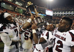 photo -   South Carolina players Jadeveon Clowney (7), Shaq Wilson (54), Akeem Auguste (3) and Brison Williams (12) carry the Palmetto Bowl Trophy after an NCAA college football game against Clemson, Saturday, Nov. 24, 2012, in Clemson, S.C. South Carolina won 27-17. (AP Photo/Rainier Ehrhardt)