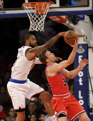 Photo - New York Knicks' Tyson Chandler, left, tries to block a shot by Chicago Bulls' Mike Dunleavy during the first half of the NBA basketball game, Sunday, April 13, 2014 in New York. (AP Photo/Seth Wenig)