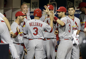 St. Louis Cardinals' Carlos Beltran (3) is greeted in the dugout by teammates after scoring off a single by teammate Yadier Molina against the San Diego Padres during the fifth inning of their baseball game Wednesday, May 22, 2013, in San Diego. (AP Photo/Gregory Bull)