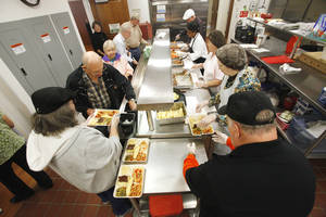 People are served in the lunch line at the Edmond Senior Center in Mitch Park Tuesday. The meal program has been popular since it began. Photos by PAUL B. SOUTHERLAND, the oklahoman