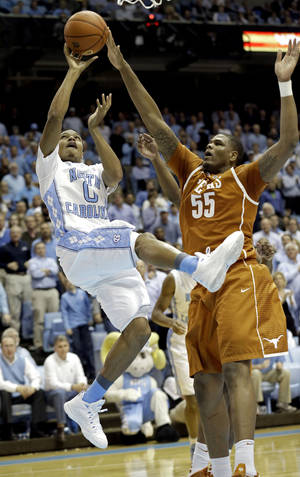 Photo - Texas' Cameron Ridley (55) defends as North Carolina's Nate Britt (0) drives to the basket during the first half of an NCAA college basketball game in Chapel Hill, N.C., Wednesday, Dec. 18, 2013. (AP Photo/Gerry Broome)