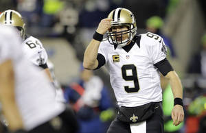 Photo - New Orleans Saints quarterback Drew Brees gestures in the second half of an NFL football game against the Seattle Seahawks, Monday, Dec. 2, 2013, in Seattle. (AP Photo/Scott Eklund)